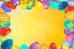 Colorful Easter egg frame edge border against a yellow background. Space for text royalty free stock photography