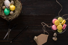 Colorful easter egg in nest on dark wood board. Royalty Free Stock Images
