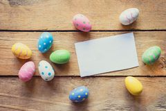 Colorful easter egg and paper card on wood background with space Royalty Free Stock Photography