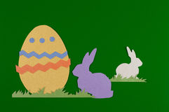 Colorful easter egg and rabbits. Colorful eggs with grass and rabbits drawn and cut on paper, easter egg on a green background royalty free stock photos