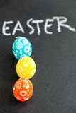 Colorful Easter egg shaped candles and text Royalty Free Stock Images