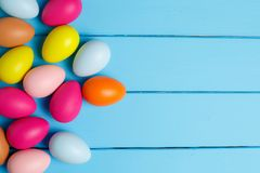 Easter eggs on wooden background with space. Colorful Easter egg side border against a blue wood background Stock Photos