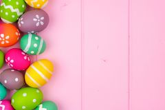 Colorful Easter egg side border against pink wood Royalty Free Stock Photography