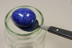 Colorful easter egg with spoon on glass. Blue colorful egg with spoon on glass Stock Photos