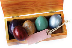 Colorful easter egg in wood box with paper tag on white background Royalty Free Stock Photo