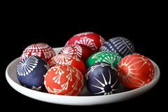 Colorful Easter eggs. On a white plate isolated on black Stock Photos