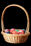 Colorful Easter eggs. In a weaved basket isolated on black Stock Photo