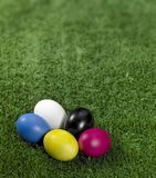 Colorful Easter eggs. Some colored Easter eggs in green artificial grass background stock photos