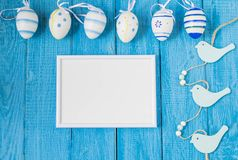 Colorful Easter Eggs arranged to one side on a blue background. stock photography