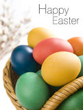 Colorful easter eggs in a basket. Some catkins in background. Space for your text royalty free stock photos