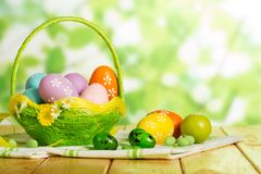 Colorful Easter eggs in basket, candy, napkins on abstract green. Colorful Easter eggs in a basket and near, candy, cloth napkins on an abstract green background Royalty Free Stock Photos