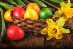 Colorful Easter eggs in basket on dark wooden background. Colorful Easter eggs in a basket on dark wooden background Royalty Free Stock Images