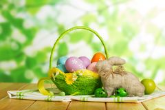 Colorful Easter eggs in basket and easter bunny, candy, ribbon. Colorful Easter eggs in a basket and easter bunny, candy, ribbon on abstract green background Stock Photo