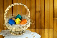 Colorful Easter eggs in a basket. Filled with hay. The basket is standing on a napkin. In the background you can see the boards Stock Photos