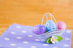 Colorful Easter eggs in basket with flower on fabric on wooden b Royalty Free Stock Photography