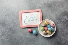 Colorful easter eggs in basket and flowers on table. Top view with copy space stock photography