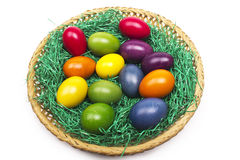 Colorful Easter eggs in a basket on the gras Royalty Free Stock Images
