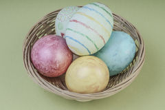 Colorful easter eggs in a basket. On green background Stock Photography