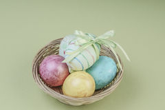 Colorful easter eggs in a basket. On green background Royalty Free Stock Photos