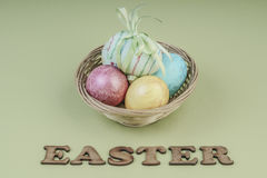 Colorful easter eggs in a basket. On green background Stock Photo