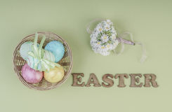 Colorful easter eggs in a basket. On green background Royalty Free Stock Images