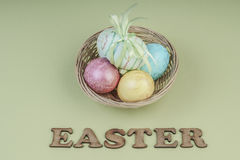 Colorful easter eggs in a basket. On green background Stock Images