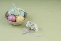 Colorful easter eggs in a basket on green. Background Stock Photo