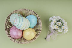 Colorful easter eggs in a basket on green. Background Stock Image