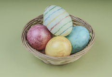 Colorful easter eggs in a basket on green. Background Royalty Free Stock Image