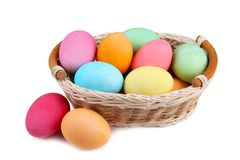 Colorful easter eggs in basket isolated on white background royalty free stock photography