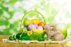 Colorful Easter eggs in basket, large egg, entwined in twine, bu. Colorful Easter eggs in a basket next to one large egg and two entwined in twine, easter bunny Stock Images