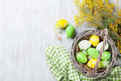 Colorful easter eggs in basket and mimosa. Flowers on wooden table. Top view with copy space Stock Image