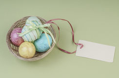 Colorful easter eggs in a basket with name tag. Colorful easter eggs in a basket on green background Royalty Free Stock Photos