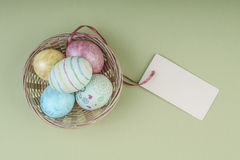Colorful easter eggs in a basket with name tag. Colorful easter eggs in a basket on green background with an empty name tag Royalty Free Stock Image