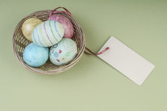 Colorful easter eggs in a basket with name tag. Colorful easter eggs in a basket on green background with an empty name tag Stock Images
