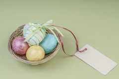 Colorful easter eggs in a basket with name tag. Colorful easter eggs in a basket on green background with an empty name tag Royalty Free Stock Photo