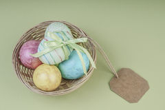 Colorful easter eggs in a basket with name tag. Colorful easter eggs in a basket on green background with an empty name tag Royalty Free Stock Photography