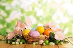 Colorful Easter eggs in basket and near, candy, grass, flowers. Colorful Easter eggs in a basket and near, candy, grass, branch with flowers on the abstract Royalty Free Stock Photos