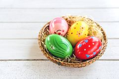 Colorful easter eggs in basket nest decoration on white wooden. Background royalty free stock image