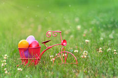 Colorful Easter eggs in the basket of a tricycle. Colorful Easter eggs in the basket of a pink tricycle in the grass Royalty Free Stock Photo