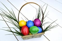 Colorful Easter eggs in basket theme. Colorful Easter eggs in a basket on a white background with fresh grass Stock Images
