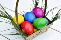 Colorful Easter eggs in basket theme. Colorful Easter eggs in a basket on a white background with fresh grass Stock Photography