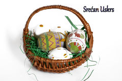 Colorful easter eggs in a basket. Colorful easter eggs in basket on a white backgroundm with happy easter written in Serbian Royalty Free Stock Photography