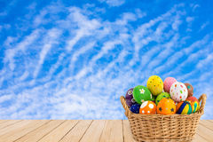 Colorful Easter eggs in a basket on wood texture on blue sky bac Stock Image