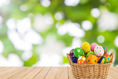 Colorful Easter eggs in a basket on wood texture on green bokeh Royalty Free Stock Photography