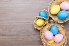 Easter eggs in the basket on wooden background royalty free stock image