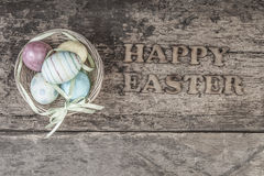 Colorful easter eggs in a basket. On wooden background Stock Images