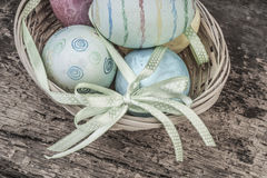 Colorful easter eggs in a basket. On wooden background Stock Photo