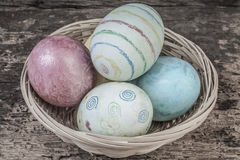 Colorful easter eggs in a basket. On wooden background Royalty Free Stock Images