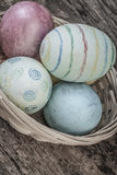 Colorful easter eggs in a basket. On wooden background Stock Photos